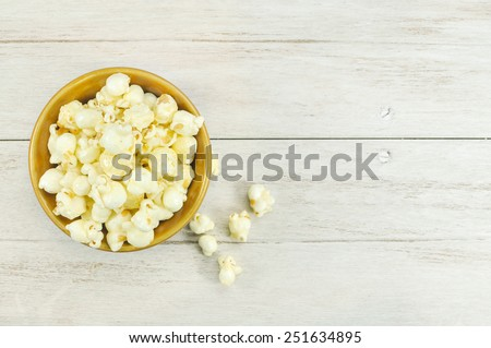 popcorn in brown bowl on white wooden table. - stock photo