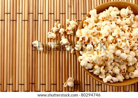 popcorn in brown bowl over mat - stock photo