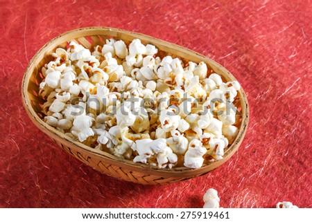 popcorn in bucket over red velvet cloth - stock photo