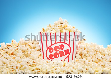 Popcorn in classic box overflowing with freshly popped corn against a blue background - stock photo