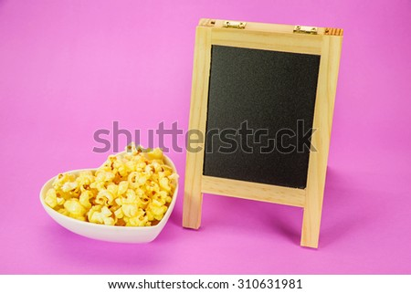 popcorn in heart shape bowl and chalk board - stock photo