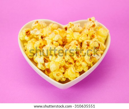 popcorn in heart shape bowl on pink background - stock photo