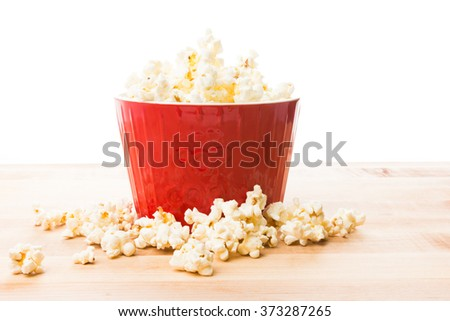 Popcorn in large red bowl on wood table