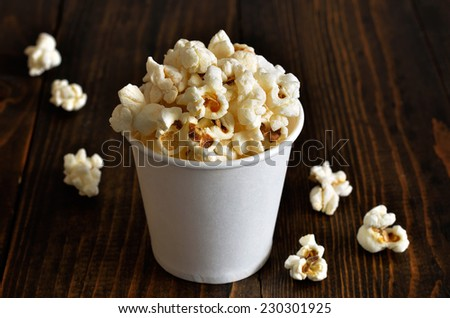 Popcorn in paper bucket on a brown wooden background - stock photo