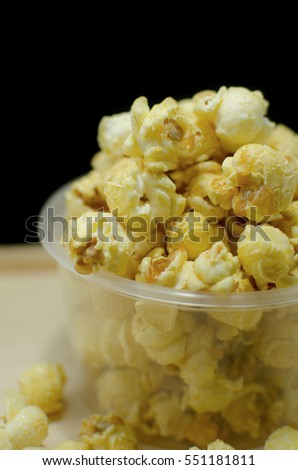 Popcorn in plastic glass on wood table with dark background.