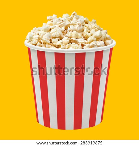 Popcorn in red striped bucket on yellow background - stock photo
