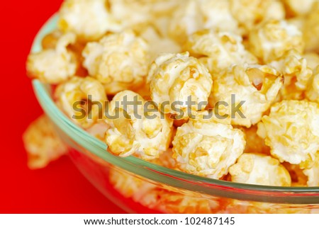 Popcorn in the bowl on red background - stock photo