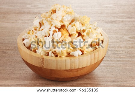 popcorn in wooden bowl on wooden table - stock photo