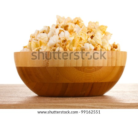 popcorn in wooden bowl on wooden table on white background - stock photo