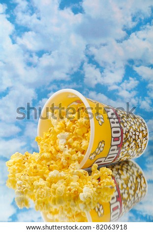 Popcorn on glass with cloud background and container