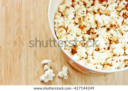 Popcorn on wooden background top view - stock photo
