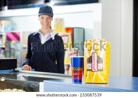 Popcorn paperbag and drink on concession stand at cinema with female worker standing in background - stock photo