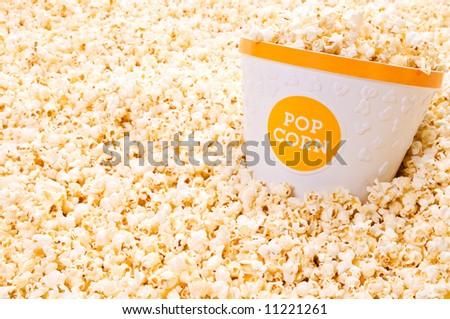 Popcorn tub on a background of popcorn - stock photo