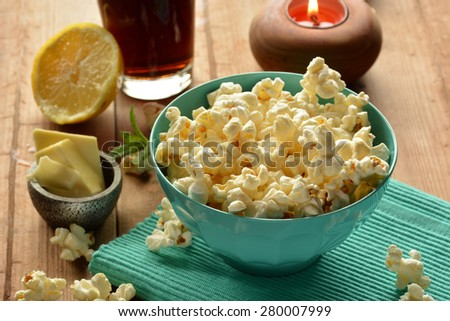 popcorn with butter and salt accompanied by cola - stock photo