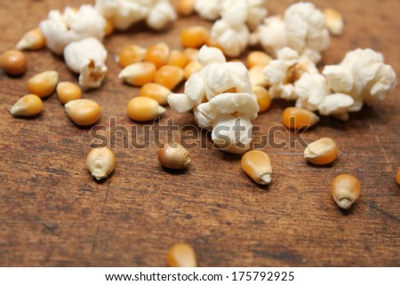 Popped popcorn and kernels over wood background - stock photo