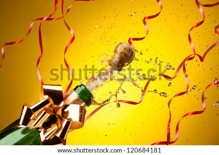 Popping cork from Champaign bottle with gold bow and ribbons on background, with splashes all around the yellow background - stock photo