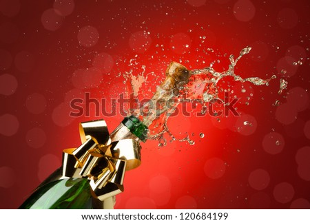 Popping cork from Champaign bottle with lot's of splashes red background - stock photo