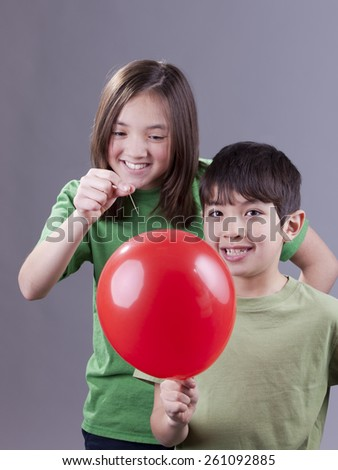 Popping her brother's balloon. - stock photo