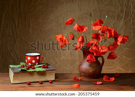 Poppy flowers in a vase woth a book on a wooden book - stock photo
