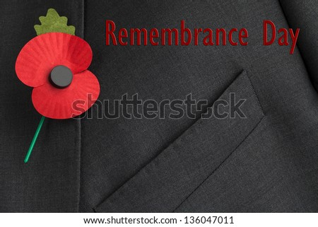 Poppy for Poppy Day on suit lapel with 'Remembrance Day,' in red writing. - stock photo