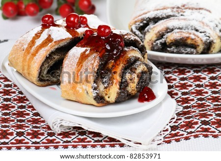 Poppy seed cake with jam decorated by powdered sugar and berries. - stock photo