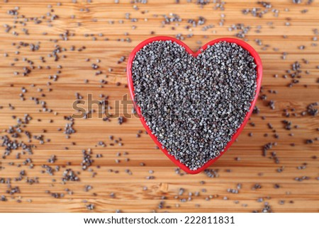 Poppy seeds in a heart bowl. Close-up. - stock photo