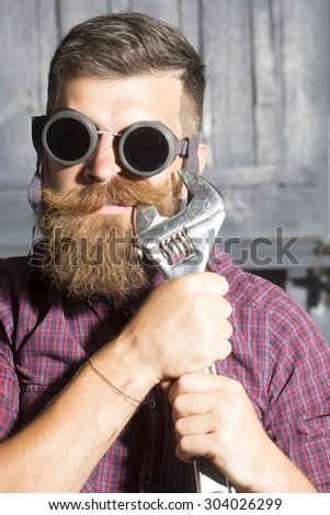 Poprtrait of young crazy man in purple checkered shirt and aviator glasses standing in garage holding iron metallized spanner near mouth on workshop background, vertical picture - stock photo