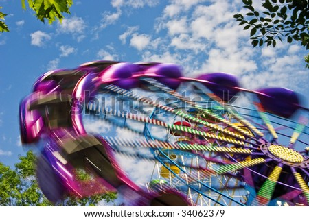 Popular attraction in park - a Ferris wheel on a background of the cloudy blue sky - stock photo