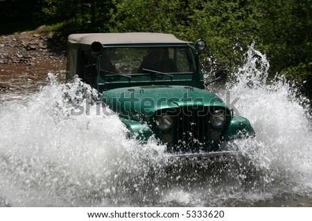 Popular four-wheel-drive vehicle plows through mountain stream creating large spray of water - stock photo