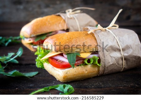 Popular panini sandwiches with ham and cheese on the wooden background,selective focus - stock photo