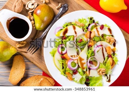 popular pear salad with walnut, fried chicken breast. red onion, lettuce leaves and cranberry on the white dish with caramelized balsamic sauce in the gravy boat, selective focus, close-up - stock photo
