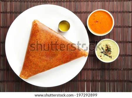 Popular south indian breakfast ghee roast  dosa in golden brown color with 3 types of side dishes. - stock photo