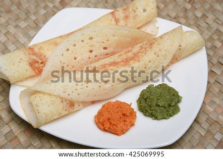 Popular traditional South Indian breakfast meal masala dosa / set dosa / ghee roast with coconut / tomato chutney and coriander chutney, Kerala, India.