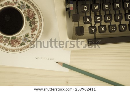 Porcelain coffee cup, old typewriter and I love you message on wooden table. Old photo style - stock photo