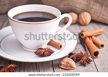 Porcelain coffee cup on the table. Garnish with star anise, cinnamon, nuts.Christmas time.  - stock photo