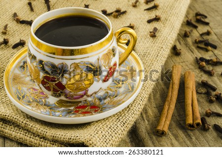 Porcelain coffee cup with floral motif on wooden table - stock photo
