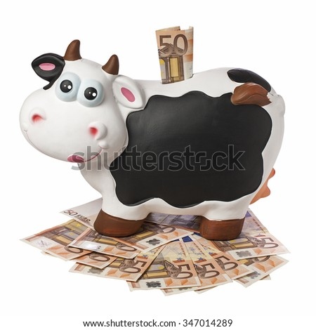 Porcelain cow piggybank with 50 euro inserted on 50 euro banknotes floor isolated and  blank blackboard copyspace - stock photo
