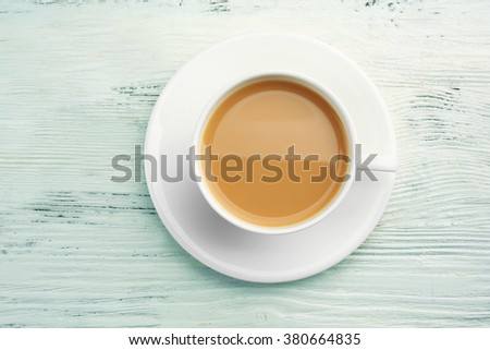 Porcelain cup of tea with milk on white wooden background - stock photo