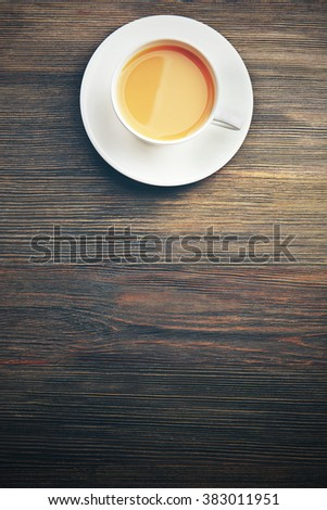 Porcelain cup of tea with milk on wooden background - stock photo