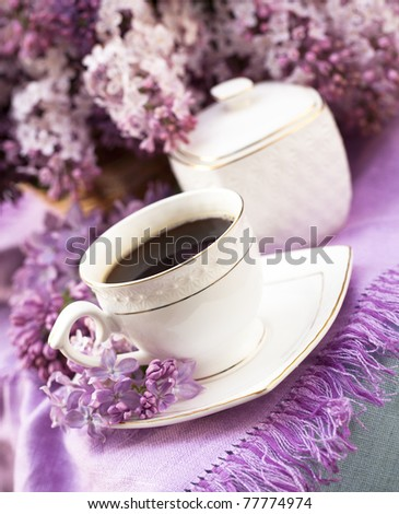 porcelain cup with coffee and lilac - stock photo