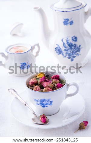 Porcelain cup with dry bud of roses with sugar bowl and teapot background  - stock photo
