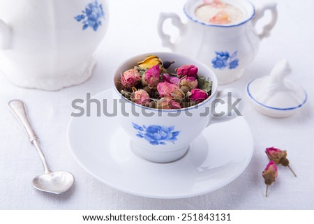 Porcelain cup with dry pink bud of roses with sugar bowl and teapot background  - stock photo