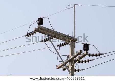 Porcelain insulator on electric pole - stock photo