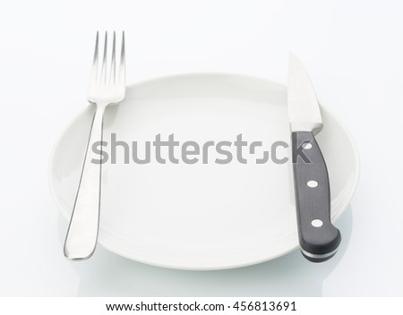 porcelain plate with knife and fork isolated on white background