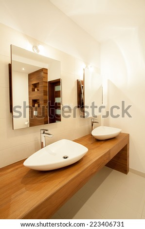 Porcelain sinks on wooden counter in bathroom - stock photo