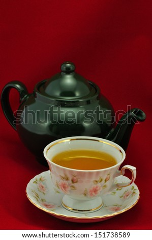 Porcelain tea cup full of tea  and green teapot on a red background - stock photo