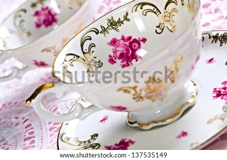 Porcelain tea cups on lace with shallow depth of field - stock photo