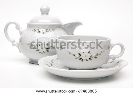 Porcelain tea pot and cup on white background