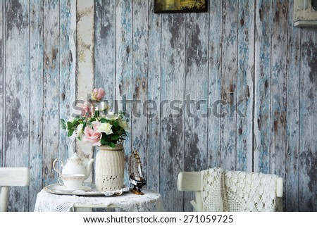 Porcelain teapot and cup on a table with a vase with artificial flowers on a background of the old wooden walls. - stock photo