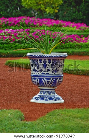 Porcelain vase with the flower as an element of landscape design - stock photo